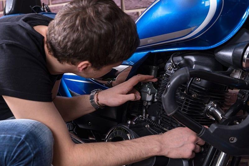 a man checking a motorbike